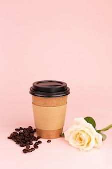 Taza, granos de café y rosa