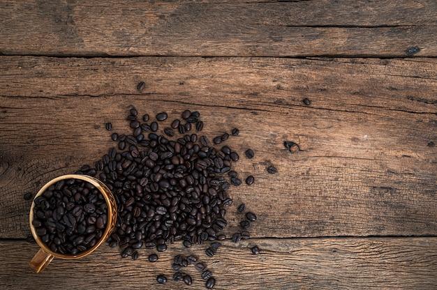 Taza de granos de café en la vista superior del escritorio