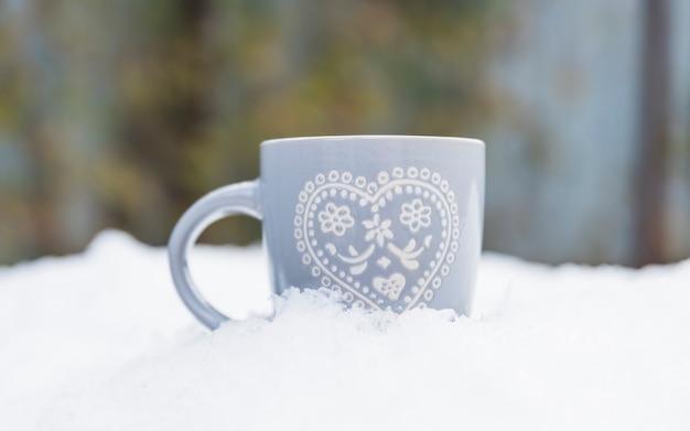 Taza gris en la nieve