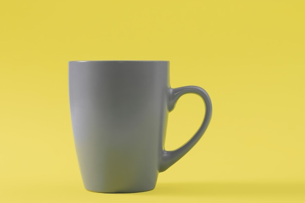 Taza gris sobre mesa amarilla. colores del año 2021, illuminating y ultimate grey.