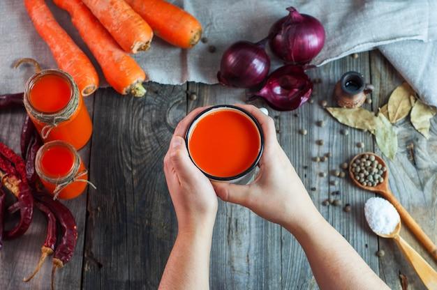 Taza de hierro con jugo de zanahoria en manos femeninas.