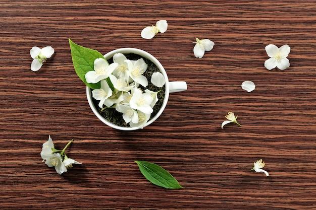 Taza de hojas de té verde y flores de jazmín en mesa de madera