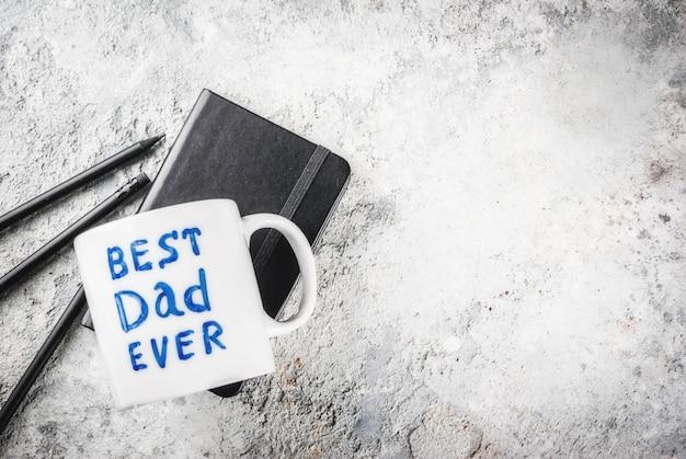 Taza con la inscripción best father ever, libreta de negocios y lápices