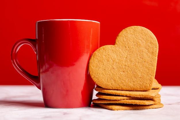 Taza junto a galletas de corazón