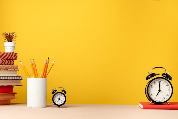 Taza de lápices y blocs de notas en el escritorio contra amarillo