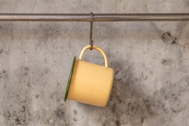 Taza de lata amarilla colgada en riel inoxidable en pared de cemento