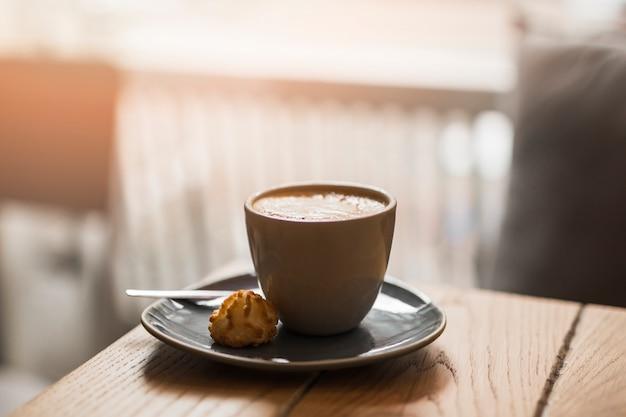 Taza de latte con galletas en el platillo sobre la mesa de madera