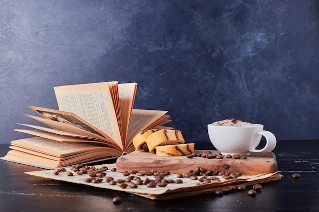 Taza de leche con café en polvo y rollcake.