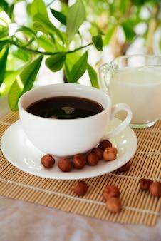 Taza de leche y café sobre estera de bambú.