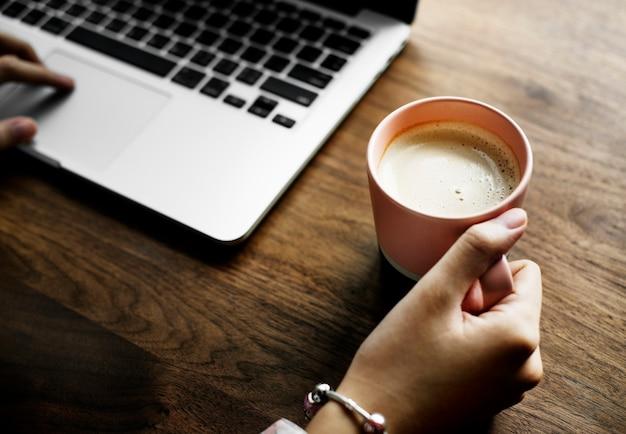 Una taza de leche caliente agradable al lado de una computadora portátil