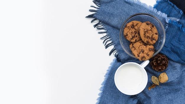 Taza de leche cerca de tazón de galletas en tela escocesa azul