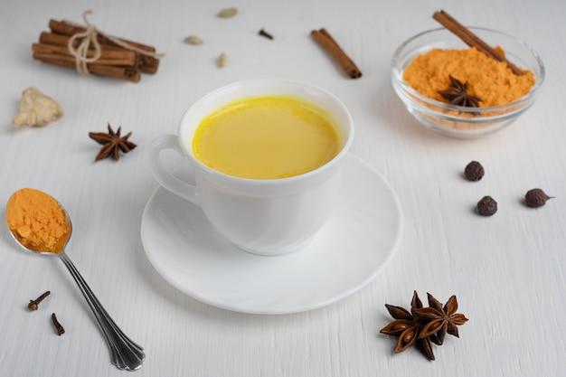 Taza de leche dorada servida en un plato con una cuchara de cúrcuma en polvo y canela en el cuadro blanco