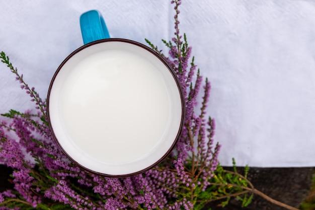 Una taza de leche y flores de brezo en una mesa de madera