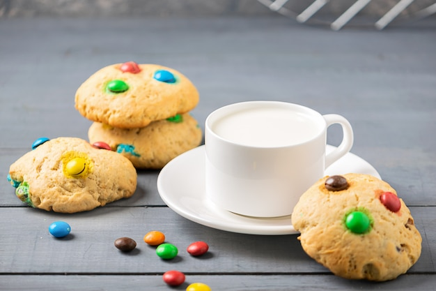 Una taza de leche y galletas decoradas con caramelos de gominolas de colores