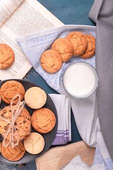 Taza de leche con galletas y libro