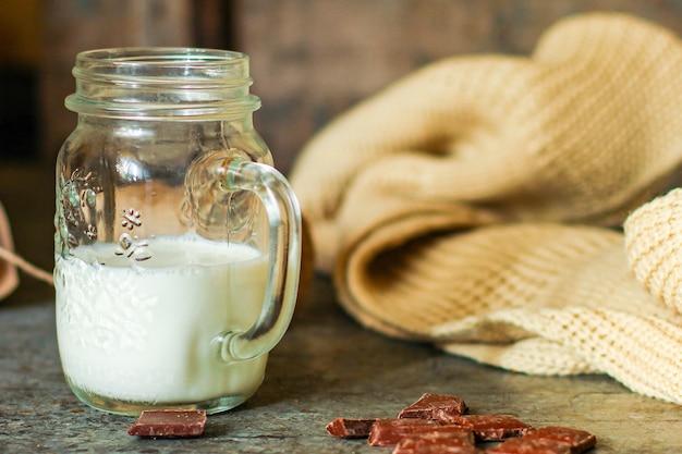 Taza de leche y galletas en la mesa hojas amarillas de otoño