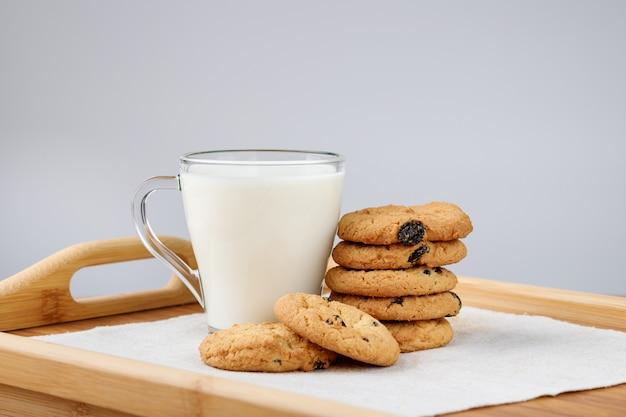 Taza de leche y galletas con pasas en una bandeja de madera