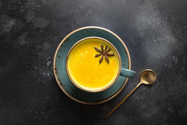 Taza de leche con leche de cúrcuma dorada ayurvédica con cúrcuma en polvo y anís estrella en negro. vista desde arriba.