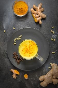Taza de leche con leche de cúrcuma dorada ayurvédica con cúrcuma en polvo y estrella de anís