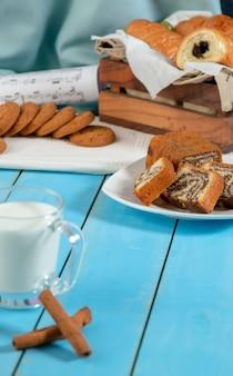 Una taza de leche con palitos de canela y una galleta en una mesa de madera azul.