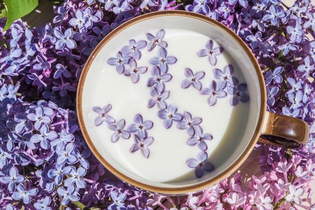 Taza con leche y pequeñas flores lilas moradas