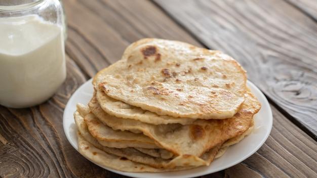 Taza de leche y un plato de tortillas de maíz frito sobre una mesa de madera con textura la vista desde la parte superior