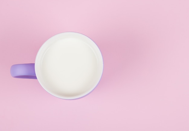 Taza de leche sobre un fondo rosa pastel