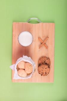 Taza de leche con tarro de galletas y canela