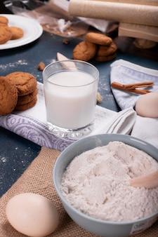 Taza de leche con tarro de galletas y harina