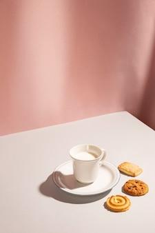 Taza de leche con variedad de galletas en la mesa