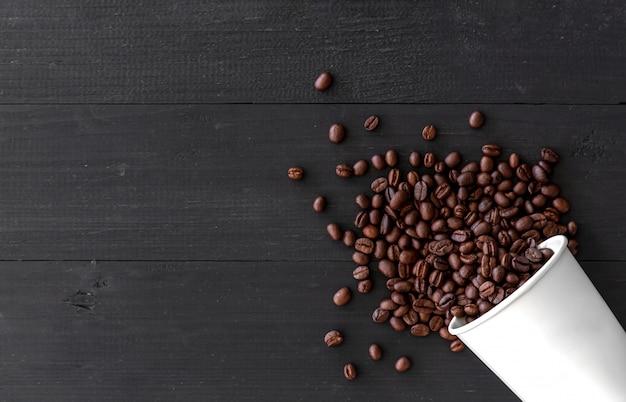 Taza del libro blanco y granos de café en viejo fondo de madera. vista superior