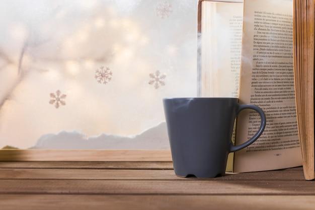 Taza y libro en mesa de madera cerca de banco de nieve y copos de nieve