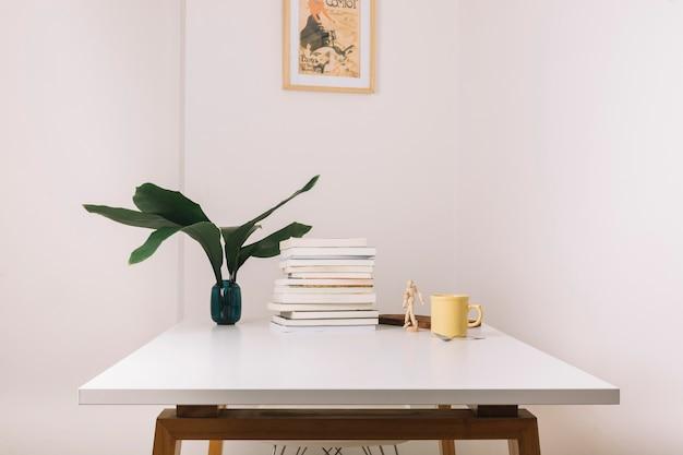 Taza y libros sobre la mesa cerca de decoraciones
