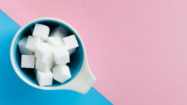 Taza llena de cubos de azúcar vista superior