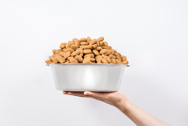 Taza llena con una diapositiva de alimento seco para mascotas aislado sobre fondo blanco.
