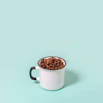 Taza llena de granos de café