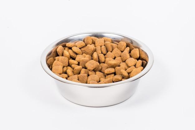 Una taza llena con pedazos de alimento seco para mascotas aislado. bol de comida de metal para perro o gato