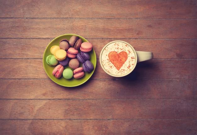 Taza y macarons sobre fondo de madera