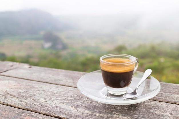 Taza de la mañana de café en la tabla de madera con la montaña en la salida del sol y el mar de la niebla, imagen con el espacio de la copia.