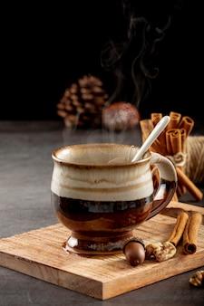 Taza marrón con palitos de canela y café sobre un soporte de madera