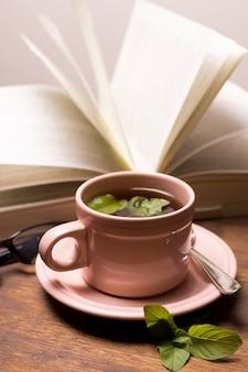 Taza marrón de té de hierbas con libro sobre la mesa