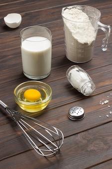 Taza de medir con harina, vaso de leche, huevo roto y sal, batidor de metal sobre la mesa. superficie de madera oscura. vista superior