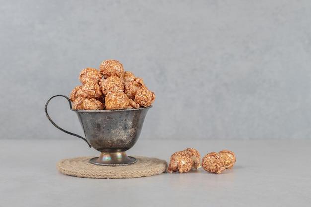 Taza de metal llena de palomitas de maíz confitadas marrones sobre mesa de mármol.