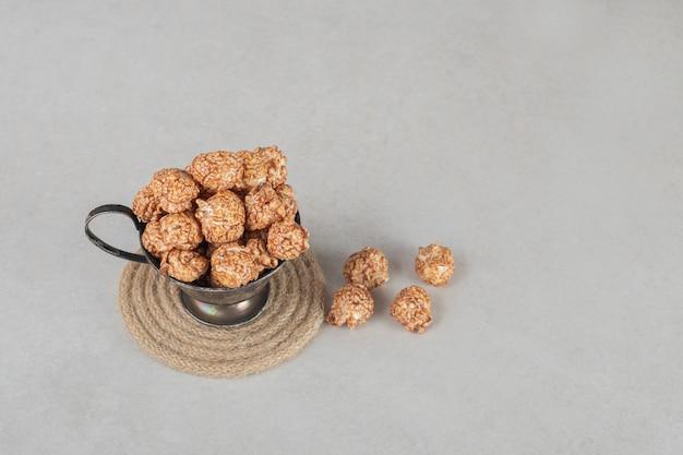 Taza de metal rebosante de palomitas de maíz confitadas marrones sobre mármol.