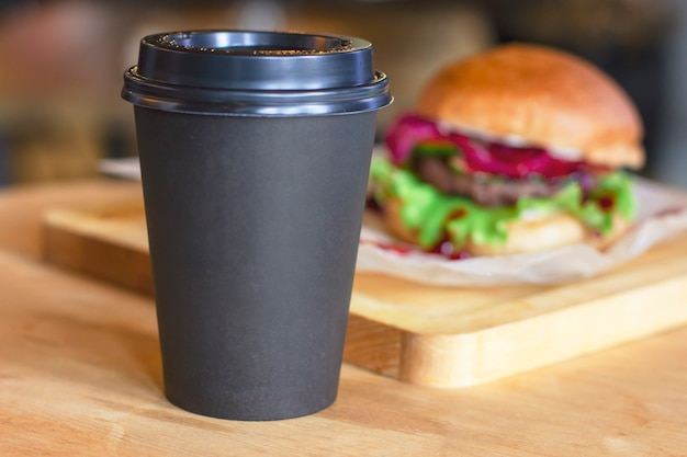 Taza negra con café para ir al fondo con hamburguesa, maqueta