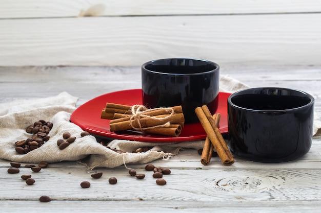 Taza negra, fondo de madera, bebidas, mañana de navidad, granos de café, ramas de canela
