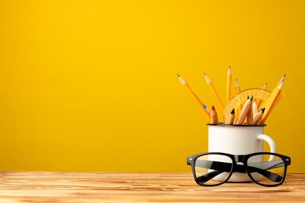 Taza de oficina con lápices y artículos de papelería contra la vista frontal de fondo amarillo