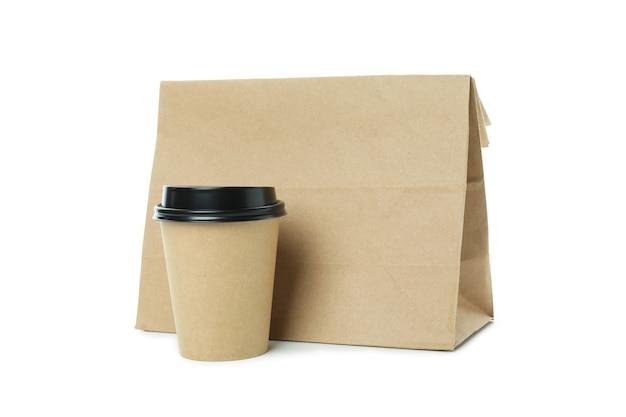 Taza de papel y bolsa de papel aislado sobre fondo blanco.