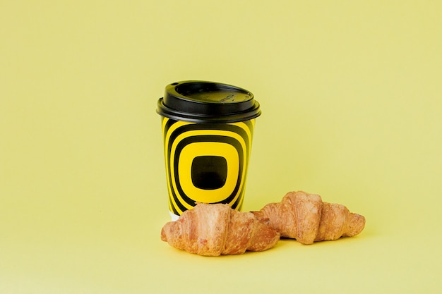 Taza de papel de café y cruasanes en amarillo