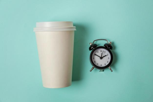 Taza de papel de café y despertador sobre fondo azul.